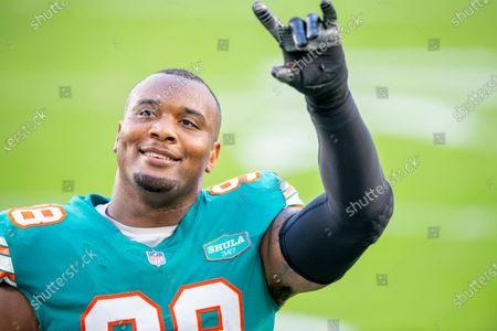 Miami Dolphins defensive tackle Raekwon Davis (98) smiles and gestures on the field after the Dolphins defeated the New England Patriots during an NFL football game, in Miami Gardens, Fla