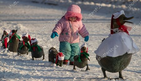 A child plays with a bronze monument by Boston sculptor Nancy Schon one duck and eight ducklings dressed as Father Frost on the Novodevichy park in Moscow, Russia, 27 December 2020. The duck family came to Moscow as a gift from the US first lady Barbara Bush. Russian President Mikhail Gorbachev and his wife Raisa visited the US where Mrs Gorbacheva fell in love with duck family during walking in Boston Central Park. Mocsow's replica was given to Russia as part of the Strategic Arms Reduction Treaty in 1991.