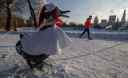 A man runs behind a bronze monument by Boston sculptor Nancy Schon one duck and eight ducklings dressed as Father Frost on the Novodevichy park in Moscow, Russia, 27 December 2020. The duck family came to Moscow as a gift from the US first lady Barbara Bush. Russian President Mikhail Gorbachev and his wife Raisa visited the US where Mrs Gorbacheva fell in love with duck family during walking in Boston Central Park. Mocsow's replica was given to Russia as part of the Strategic Arms Reduction Treaty in 1991.