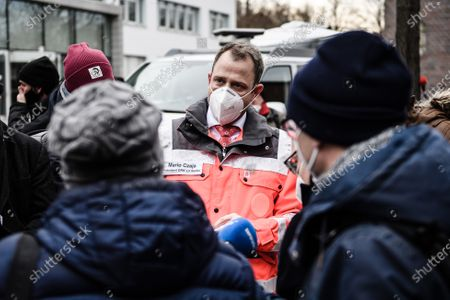 Berlin Red Cross president Mario Czaja talks to media in front of a vaccination center in the Arena event hall on the first day of the nationwide launch of Covid-19 vaccinations during the second wave of the coronavirus pandemic in Berlin, Germany, 27 December 2020. Germany is beginning the vaccinations on 27 December mainly with mobile teams who are inoculating senior citizens in nursing homes. The volume of delivered vaccine is to rise sharply next week and many mass vaccination centers will open their doors in early January.