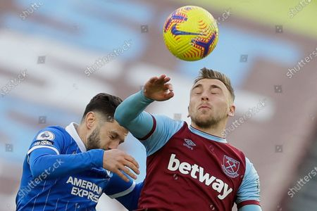 West Ham's Jarrod Bowen heads the ball before Brighton's Adam Lallana, left, during the English Premier League soccer match between West Ham and Brighton in London, England