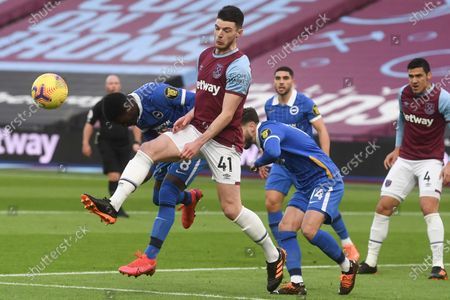 West Ham's Declan Rice, second left, clears the ball from a corner before Brighton's Yves Bissouma, left, and Brighton's Adam Lallana, center right, can try to score during the English Premier League soccer match between West Ham and Brighton in London, England