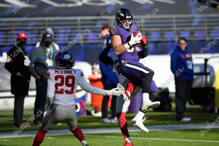 Baltimore Ravens tight end Mark Andrews (89) makes a catch against New York Giants free safety Logan Ryan, back, and safety Xavier McKinney (29) during the first half of an NFL football game, in Baltimore