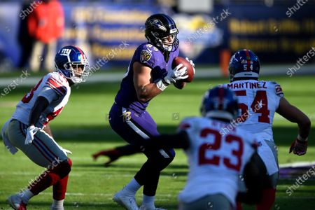 Baltimore Ravens tight end Mark Andrews, center, makes a catch as New York Giants linebacker Tae Crowder (48), inside linebacker Blake Martinez (54) and free safety Logan Ryan (23) move in to tackle him during the first half of an NFL football game, in Baltimore