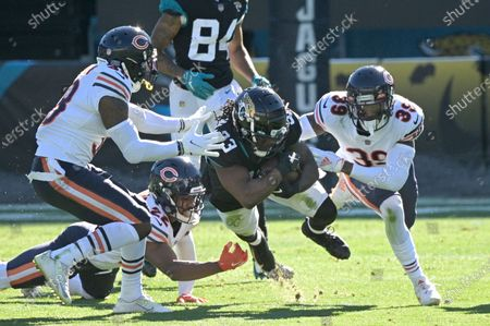 Jacksonville Jaguars running back Dare Ogunbowale (33) is tackled by Chicago Bears safety Tashaun Gipson Sr., left, cornerback Kindle Vildor (22) and safety Eddie Jackson (39) after rushing for yardage during the first half of an NFL football game, in Jacksonville, Fla