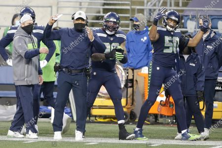 Seattle Seahawks linebacker K.J. Wright (50) and defensive coordinator Ken Norton Jr., second from left, gesture during the second half of an NFL football game against the Los Angeles Rams, in Seattle