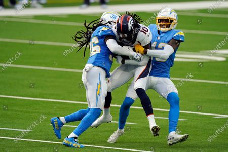 Denver Broncos wide receiver Jerry Jeudy (10) is tackled by Los Angeles Chargers strong safety Jahleel Addae, left, and cornerback Michael Davis during the first half of an NFL football game, in Inglewood, Calif