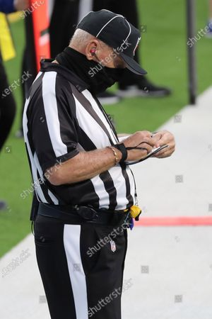 Field judge Tom Hill (97) records a timeout during an NFL football game between the Denver Broncos and the Los Angeles Chargers, in Inglewood, Calif