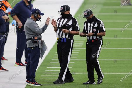 Stock Photo of Field judge Tom Hill (97) and line judge Carl Johnson (101) talk with Denver Broncos head coach Vic Fangio during an NFL football game against the Los Angeles Chargers, in Inglewood, Calif
