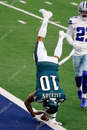 Philadelphia Eagles wide receiver DeSean Jackson (10) leaps into the end zone after catching a touchdown pass as Dallas Cowboys cornerback Trevon Diggs (27) looks on in the first half of an NFL football game in Arlington, Texas, Sunday, Dec. 27. 2020