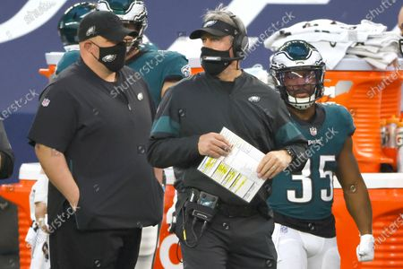 Philadelphia Eagles head coach Doug Pederson works from the sidelines against the Dallas Cowboys during an NFL football game in Arlington, Texas