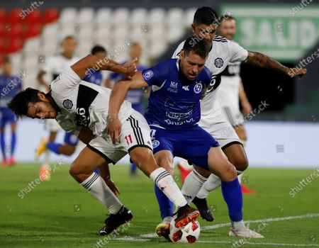 Stock Photo of Nildo Viera (C) of Sol de America vies for the ball with Ivan Torres (L) and Diego Torres of Olimpia during their Clausura tournament seminfinals soccer match at Defensores del Chaco satadium in Asuncion, Paraguay, 27 December 2020.