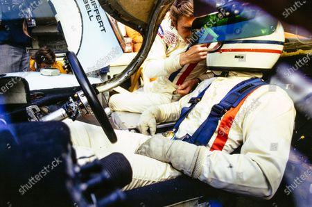 Jo Siffert talks to Derek Bell as he sits in the cockpit of their John Wyer Automotive Engineering Porsche 917 LH.