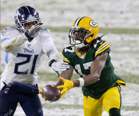 Green Bay Packers wide receiver Davante Adams (17) catches a ball in front of Tennessee Titans cornerback Malcolm Butler (21) during an NFL football game, Sunday, Dec 27. 2020, between the Tennessee Titans and Green Bay Packers in Green Bay, Wis