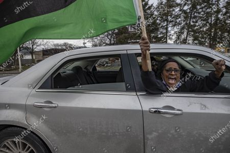 Member of the Andre' Hill Justice Caravan waves an Afro-American flag out of the window of their car. Advocates against police brutality met up at Genoa Park in Columbus, Ohio to form a Black Lives Matter Car Caravan in reaction to police officer Adam Coy killing Andre' Hill on Tuesday Dec. 22, 2020. The Caravan started in Genoa and ended in Livingston Heights. This event was organized by Consistency Speaks and the Downtowners Collective in Columbus, Ohio.