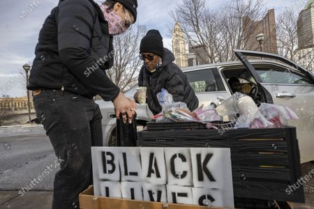Food Not Bombs distributes supplies to a member of the Andre' Hill Justice Caravan. Advocates against police brutality met up at Genoa Park in Columbus, Ohio to form a Black Lives Matter Car Caravan in reaction to police officer Adam Coy killing Andre' Hill on Tuesday Dec. 22, 2020. The Caravan started in Genoa and ended in Livingston Heights. This event was organized by Consistency Speaks and the Downtowners Collective in Columbus, Ohio.