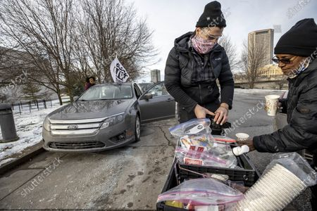 Stock Image of Food Not Bombs distributes supplies to a member of the Andre' Hill Justice Caravan. Advocates against police brutality met up at Genoa Park in Columbus, Ohio to form a Black Lives Matter Car Caravan in reaction to police officer Adam Coy killing Andre' Hill on Tuesday Dec. 22, 2020. The Caravan started in Genoa and ended in Livingston Heights. This event was organized by Consistency Speaks and the Downtowners Collective in Columbus, Ohio.