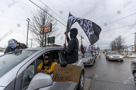 Members of the Andre' Hill Justice Caravan wave flags and placards out of their cars as they move east in Columbus. Advocates against police brutality met up at Genoa Park in Columbus, Ohio to form a Black Lives Matter Car Caravan in reaction to police officer Adam Coy killing Andre' Hill on Tuesday Dec. 22, 2020. The Caravan started in Genoa and ended in Livingston Heights. This event was organized by Consistency Speaks and the Downtowners Collective in Columbus, Ohio.