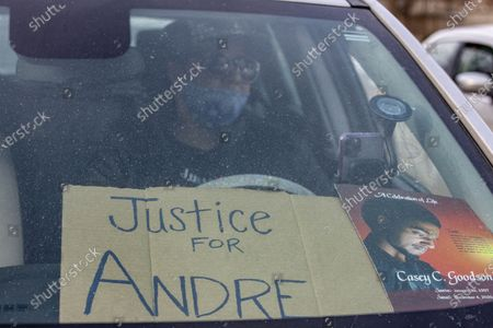Member of the Andre' Hill Justice Caravan displays placards on her dashboard. Advocates against police brutality met up at Genoa Park in Columbus, Ohio to form a Black Lives Matter Car Caravan in reaction to police officer Adam Coy killing Andre' Hill on Tuesday Dec. 22, 2020. The Caravan started in Genoa and ended in Livingston Heights. This event was organized by Consistency Speaks and the Downtowners Collective in Columbus, Ohio.