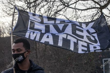 Protesters in support of black lives holds a flag during a protest against the death of Andre' Hill. Advocates against police brutality met up at Genoa Park in Columbus, Ohio to form a Black Lives Matter Car Caravan in reaction to police officer Adam Coy killing Andre' Hill on Tuesday Dec. 22, 2020. The Caravan started in Genoa and ended in Livingston Heights. This event was organized by Consistency Speaks and the Downtowners Collective in Columbus, Ohio.