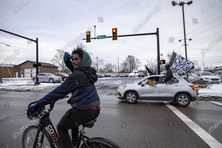 A man on bicycle rides along with the Andre' Hill Justice Caravan. Advocates against police brutality met up at Genoa Park in Columbus, Ohio to form a Black Lives Matter Car Caravan in reaction to police officer Adam Coy killing Andre' Hill on Tuesday Dec. 22, 2020. The Caravan started in Genoa and ended in Livingston Heights. This event was organized by Consistency Speaks and the Downtowners Collective in Columbus, Ohio.