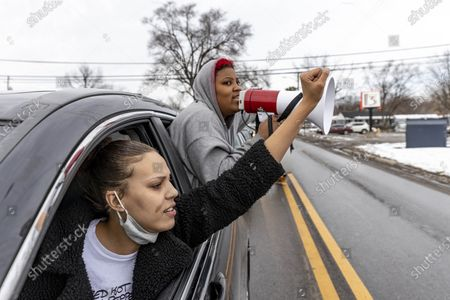 Members of the Andre' Hill Justice Caravan raise their fists while speaking through bullhorns out of their car windows. Advocates against police brutality met up at Genoa Park in Columbus, Ohio to form a Black Lives Matter Car Caravan in reaction to police officer Adam Coy killing Andre' Hill on Tuesday Dec. 22, 2020. The Caravan started in Genoa and ended in Livingston Heights. This event was organized by Consistency Speaks and the Downtowners Collective in Columbus, Ohio.
