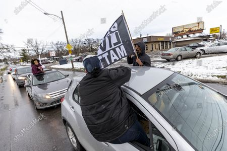 Members of the Andre' Hill Justice Caravan wave flags while communicating with one another in Livingston Heights. Advocates against police brutality met up at Genoa Park in Columbus, Ohio to form a Black Lives Matter Car Caravan in reaction to police officer Adam Coy killing Andre' Hill on Tuesday Dec. 22, 2020. The Caravan started in Genoa and ended in Livingston Heights. This event was organized by Consistency Speaks and the Downtowners Collective in Columbus, Ohio.