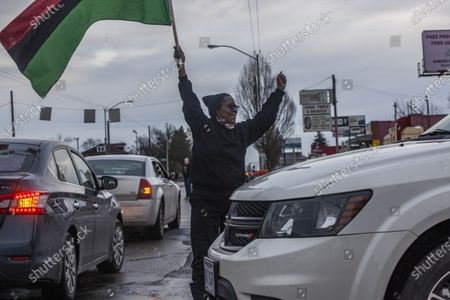 Member of the Andre' Hill Justice Caravan holds Afro-American flag in the middle of traffic. Advocates against police brutality met up at Genoa Park in Columbus, Ohio to form a Black Lives Matter Car Caravan in reaction to police officer Adam Coy killing Andre' Hill on Tuesday Dec. 22, 2020. The Caravan started in Genoa and ended in Livingston Heights. This event was organized by Consistency Speaks and the Downtowners Collective in Columbus, Ohio.