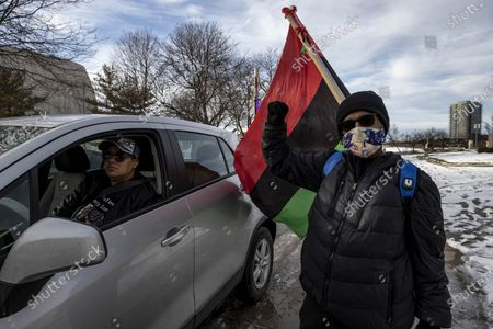 Member of the Andre' Hill Justice Caravan raises her hand with a flag on the back. Advocates against police brutality met up at Genoa Park in Columbus, Ohio to form a Black Lives Matter Car Caravan in reaction to police officer Adam Coy killing Andre' Hill on Tuesday Dec. 22, 2020. The Caravan started in Genoa and ended in Livingston Heights. This event was organized by Consistency Speaks and the Downtowners Collective in Columbus, Ohio.