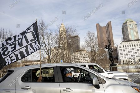 Stock Photo of Car participating in the Andre' Hill Justice Caravan waves a Black Lives Matter flag out of the window. Advocates against police brutality met up at Genoa Park in Columbus, Ohio to form a Black Lives Matter Car Caravan in reaction to police officer Adam Coy killing Andre' Hill on Tuesday Dec. 22, 2020. The Caravan started in Genoa and ended in Livingston Heights. This event was organized by Consistency Speaks and the Downtowners Collective in Columbus, Ohio.