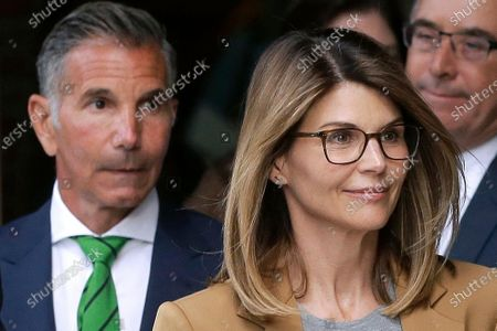 Actor Lori Loughlin, front, and husband, clothing designer Mossimo Giannulli, left, depart federal court in Boston after facing charges in a nationwide college admissions bribery scandal. Loughlin was released from federal prison in Dublin, Calif., after spending two months behind bars for paying half a million dollars in bribes to get her two daughters into college