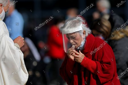 A parishioner, right, takes communion offered by Rev. Christopher Smith, rector of the cathedral, while attending a Christmas Day mass given outdoors and live-streamed on Friday, Dec. 25, 2020 in Garden Grove, CA. On November 16, 2020 Governor Gavin Newsom officially announced a change to the COVID-19 tier system to purple, the most restrictive level. This means that all Masses and gatherings may only occur outdoors and live-streamed. (Gary Coronado / Los Angeles Times)
