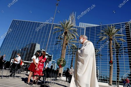 Stock Image of Rev. Christopher Smith, rector of the cathedral, in a procession to the start of the Christmas Day mass given outdoors and live-streamed at Christ Cathedral on Friday, Dec. 25, 2020 in Garden Grove, CA. On November 16, 2020 Governor Gavin Newsom officially announced a change to the COVID-19 tier system to purple, the most restrictive level. This means that all Masses and gatherings may only occur outdoors and live-streamed. (Gary Coronado / Los Angeles Times)