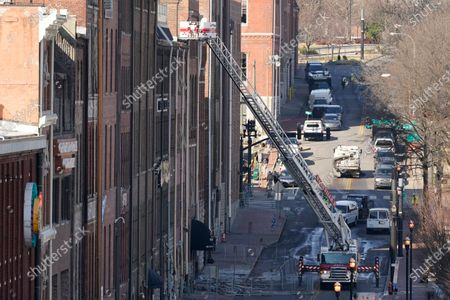 Firefighters ride in an aerial ladder as they inspect buildings damaged in a Christmas Day explosion, in Nashville, Tenn. Federal officials now turn to exploring the monumental task of piecing together the motive behind the bombing that severely damaged dozens of downtown Nashville buildings and injured three. Officials have named 63-year-old Anthony Quinn Warner as the man behind the mysterious explosion in which he was killed, but the motive has remained elusive