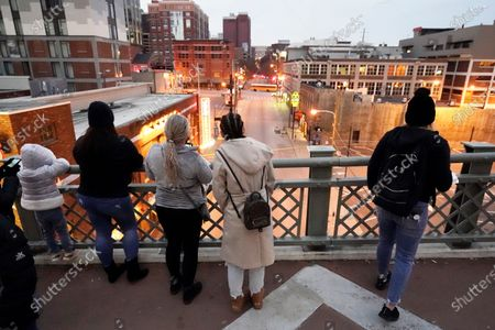 People look from a pedestrian bridge, to view the area several blocks away where an explosion took place Christmas Day in Nashville, Tenn. Federal officials now turn to exploring the monumental task of piecing together the motive behind the bombing that severely damaged dozens of downtown Nashville buildings and injured three. Officials have named 63-year-old Anthony Quinn Warner as the man behind the mysterious explosion in which he was killed, but the motive has remained elusive