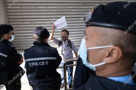 A man holds a placard outside the Eastern Magistrates' Court. Former opposition lawmaker Lam Cheuk-ting was arrested for allegedly disclosing the personal information of individuals being investigated by police in relation to the Yuen Long mob attacks last July. Officers from the Independent Commission against Corruption (ICAC) arrested the Democratic Party member at his home and brought him to North Point police station.