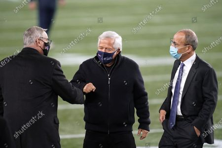 Buffalo Bills owner Terry Pegula, left, greets New England Patriots owner Robert Kraft, center, and his son, team president Jonathan Kraft before an NFL football game, in Foxborough, Mass