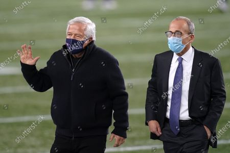 New England Patriots owner Robert Kraft, left, and his son, team president Jonathan Kraft, right, walk toward Buffalo Bills owner Terry Pegula before an NFL football game, in Foxborough, Mass