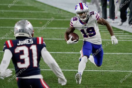 Buffalo Bills wide receiver Isaiah McKenzie, right, carries the ball as New England Patriots defensive back Jonathan Jones (31) defends in the first half of an NFL football game, in Foxborough, Mass