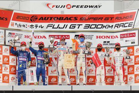 Stock Picture of GT500 Winners Heikki Kovalainen & Yuichi Nakayama ( #39 DENSO KOBELCO SARD GR Toyota Supra ) celebrate on the podium with their trophies. Alongside are second position Kazuya Oshima & Sho Tsuboi ( #14 WAKO'S 4CR GR Toyota Supra ) and third position Tomoki Nojiri & Nirei Fukuzumi ( #8 ARTA Honda NSX-GT )