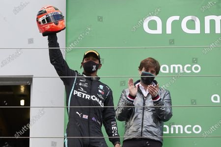 Lewis Hamilton, Mercedes-AMG Petronas F1, 1st position, arrives on the podium with the helmet of Michael Schumacher after equalling his race win record of 91