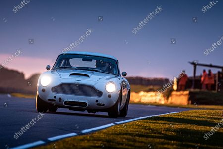 Tom Alexander/Adrian Wilmott, Aston Martin DB4GT, at dusk, in race seven, the Stirling Moss Memorial Trophy. Photo: Jayson Fong/Goodwood