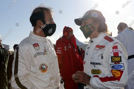 Emanuele Pirro talks to Emerson Fittipaldi in the paddock.