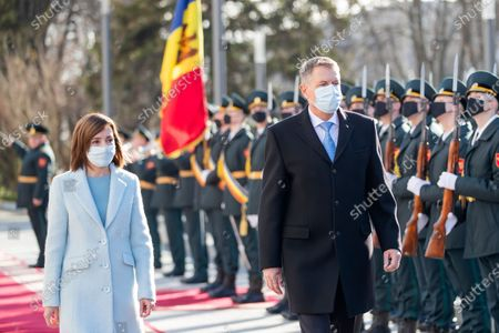 Romania's President Klaus Iohannis (R) reviews the honor guard with Moldova's President Maia Sandu (L) in front of the Presidential Palace during his first official visit in Chisinau, Moldova, 29 December 2020. President Iohannis is in Chisinau at the invitation of President Sandu. He is the first high-level visit to Chisinau after the investiture of Maia Sandu as President.