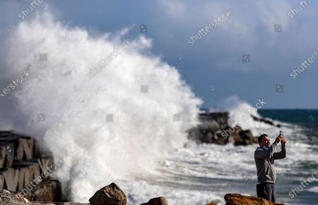 """Juan Amaya of Wilmington takes photographs as a large wave crashes against the breakwater at the Port of Los Angeles during a sunny break in a winter storm on Monday, Dec. 28, 2020 in San Pedro, CA. Amaya said he loves to come out to the coast, """"It's the only place I can breathe clean air."""" (Brian van der Brug / Los Angeles Times)"""