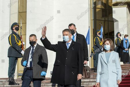 The President of Romania Klaus Iohannis (C) waves as he exits with Moldova's President Maia Sandu (R) from the Presidential Palace, during his first official visit in Chisinau, Moldova, 29 December 2020.