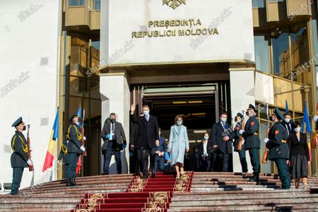 The President of Romania Klaus Iohannis (C-L) waves as he exits with Moldova's President Maia Sandu (C-R) from the Presidential Palace, during his first official visit in Chisinau, Moldova, 29 December 2020.