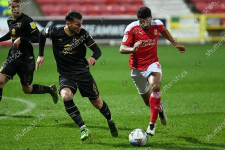 Stock Photo of Swindon Town defender Zeki Fryers (3) sprints forward with the ball under pressure from Milton Keynes Dons defender Baily Cargill (6) during the EFL Sky Bet League 1 match between Swindon Town and Milton Keynes Dons at the County Ground, Swindon