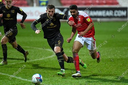 Swindon Town defender Zeki Fryers (3) sprints forward with the ball under pressure from Milton Keynes Dons defender Baily Cargill (6) during the EFL Sky Bet League 1 match between Swindon Town and Milton Keynes Dons at the County Ground, Swindon