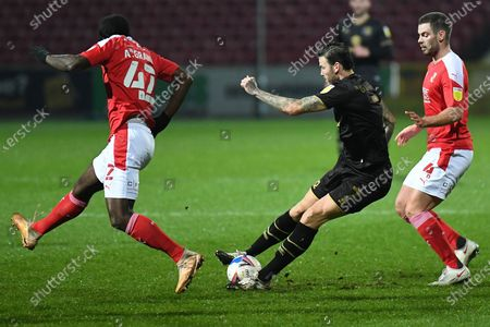 Milton Keynes Dons midfielder Ben Gladwin (7) gets a pass away under pressure from Swindon Town midfielder Anthony Grant (42) and Swindon Town defender Dion Conroy (4) during the EFL Sky Bet League 1 match between Swindon Town and Milton Keynes Dons at the County Ground, Swindon